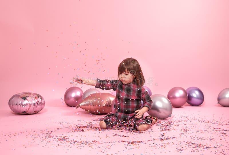 Bambino divertente che si siede su un fondo rosa Bambina divertendosi con i palloni ed i coriandoli immagini stock