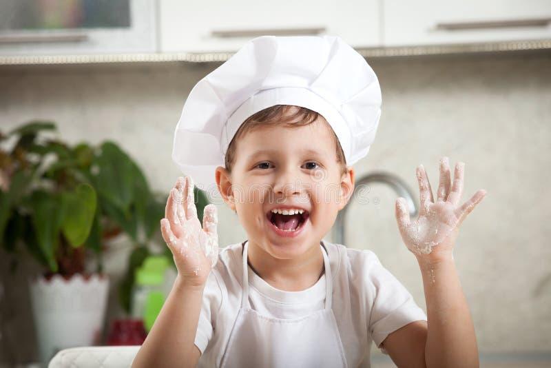 Bambino divertente con farina, sorrisi emozionali felici del ragazzo felicemente immagine stock libera da diritti