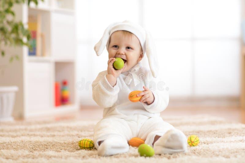 Bambino divertente in costume bianco del coniglietto che si siede sulla coperta a casa fotografie stock libere da diritti