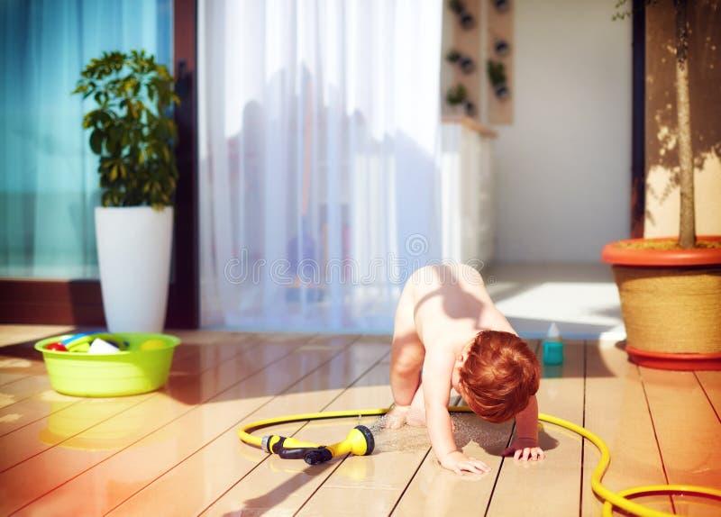 Bambino divertente del bambino che gioca con il tubo flessibile d'innaffiatura al giorno di estate immagini stock libere da diritti