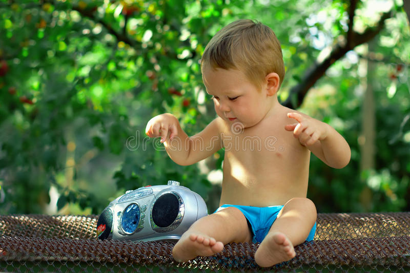 Bambino DJ che gioca con il retro registratore in giardino immagini stock