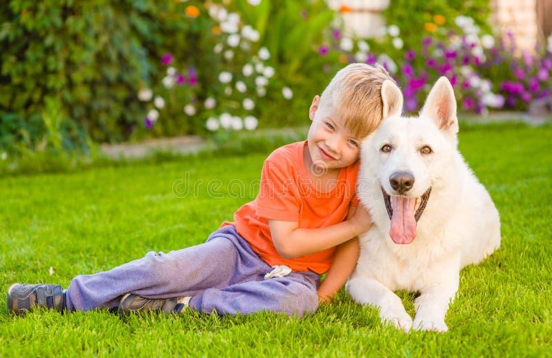Bambino e cane da pastore svizzero bianco insieme su erba verde fotografia stock
