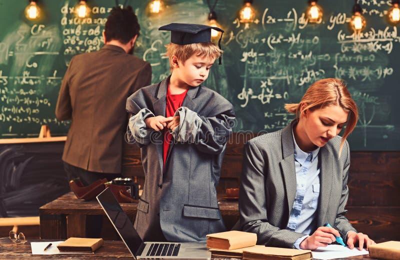Bambino e concetto di istruzione Il bambino in età prescolare del figlio insegna alla madre a scrivere, il padre attinge la lavag immagini stock