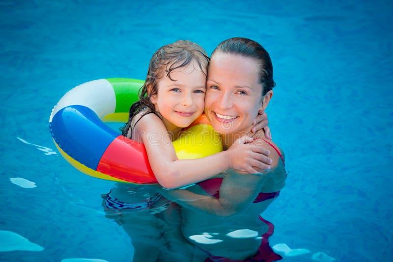 Bambino e donna che giocano nella piscina fotografie stock