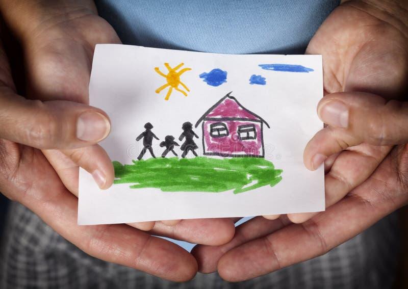 Bambino e la sua mamma che tengono una casa tirata con la famiglia immagini stock