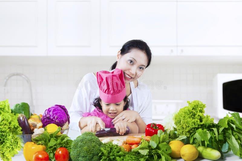 Bambino e le sue verdure di taglio della madre fotografia stock