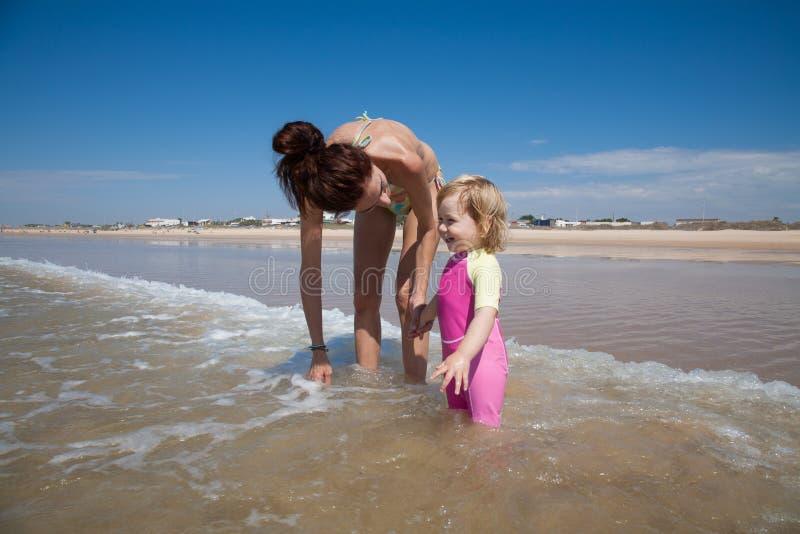 Bambino e madre sorridenti all'oceano fotografia stock