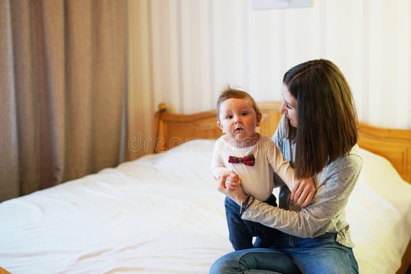Bambino e madre sul letto Mamma e neonato che giocano nella camera da letto soleggiata Genitore e bambino che si rilassano a casa immagine stock