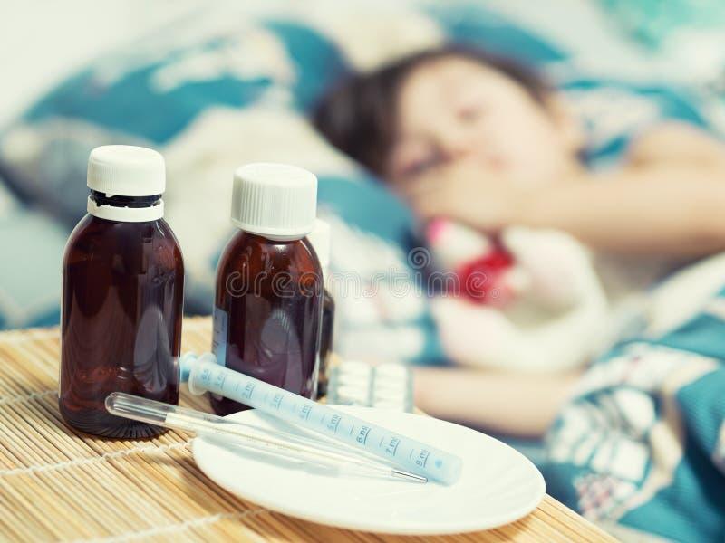 Bambino e medicina malati sulla tavola fotografie stock