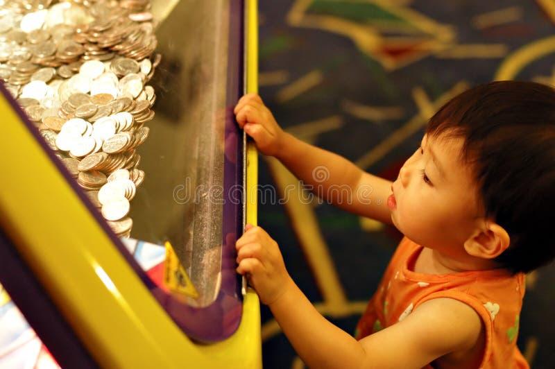 Bambino e monete brillanti immagine stock