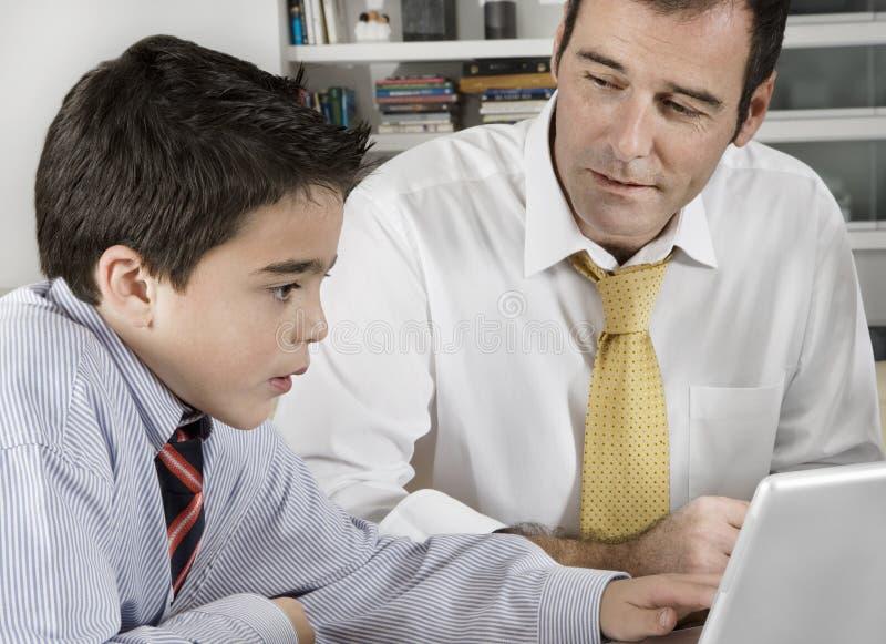 Bambino e papà sul computer portatile fotografia stock libera da diritti