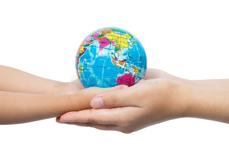 Bambino ed adulto che tengono un globo del mondo in mani fotografia stock libera da diritti