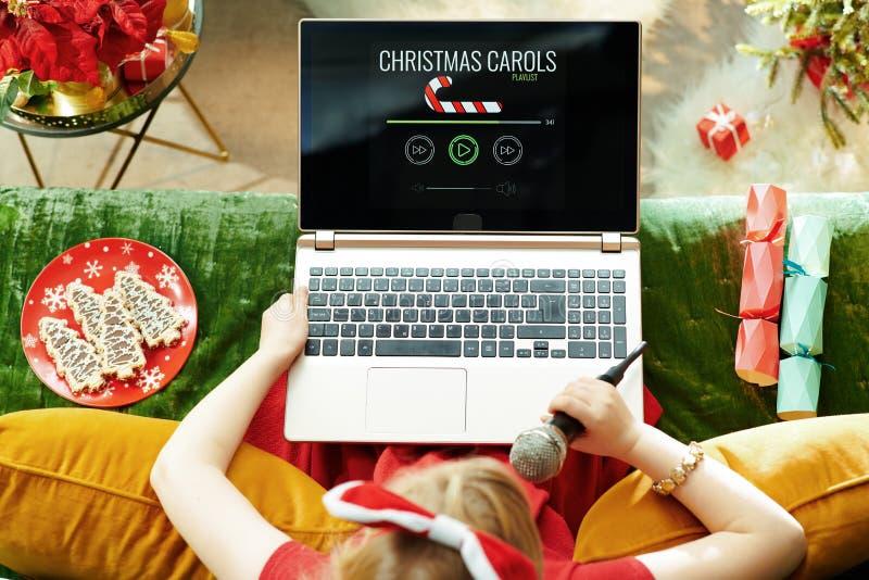 Bambino elegante canta canti natalizi mentre ascolta canzoni fotografie stock libere da diritti