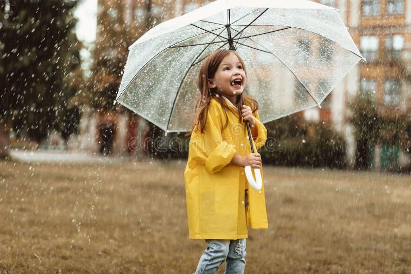 Bambino emozionante che ritiene felice circa tempo piovoso fotografie stock