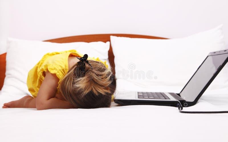 Bambino esaurito che dorme vicino ad un computer portatile fotografie stock libere da diritti