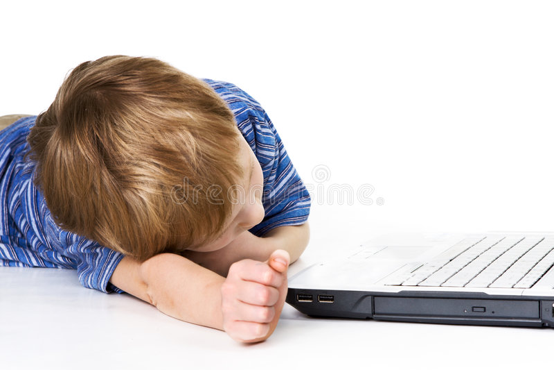 Bambino faticoso con il computer portatile fotografia stock libera da diritti