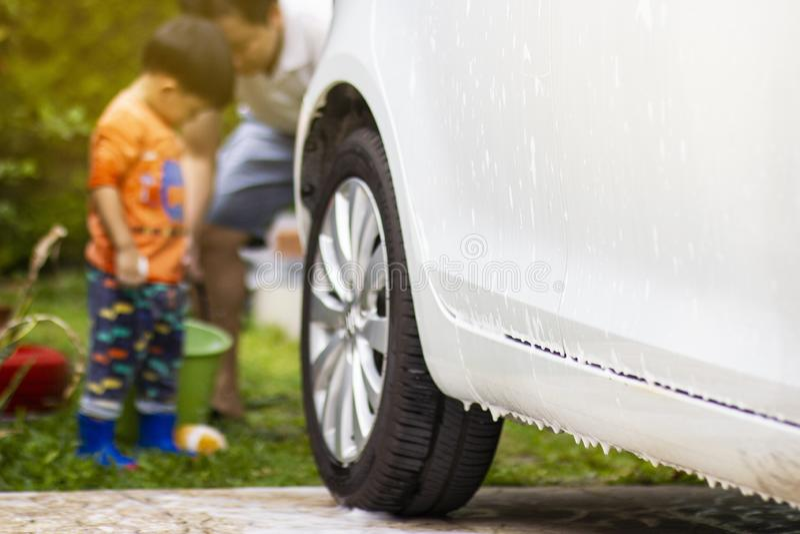 Bambino felice che è un piccolo assistente aiutando la sua pulizia di papà sull'automobile fotografia stock libera da diritti
