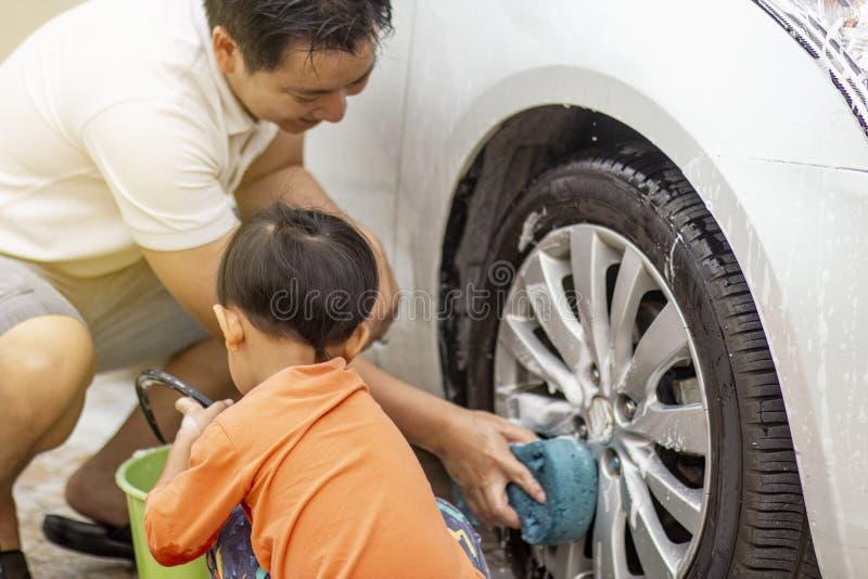 Bambino felice che è un piccolo assistente aiutando la sua pulizia di papà sull'automobile immagini stock