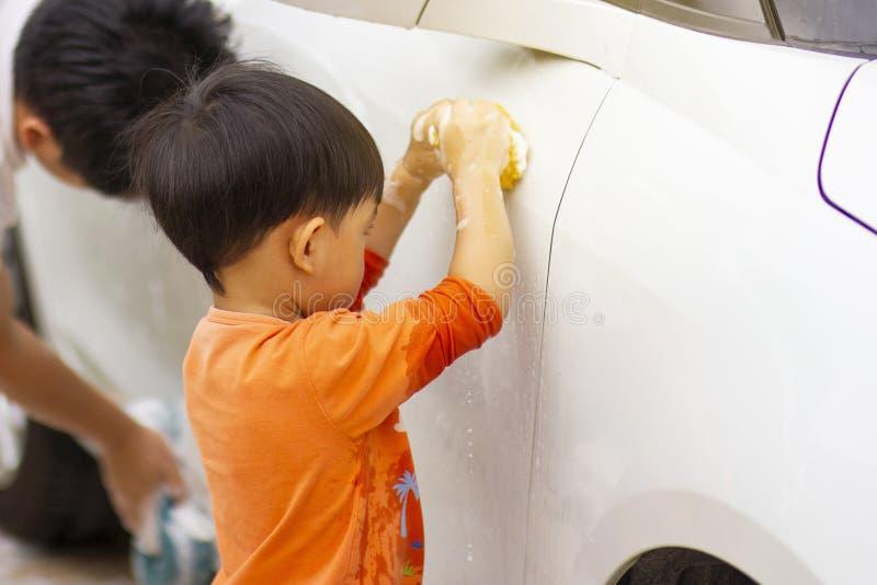 Bambino felice che è un piccolo assistente aiutando la sua pulizia di papà sull'automobile immagine stock libera da diritti