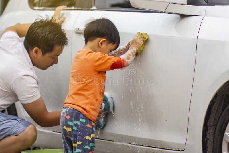 Bambino felice che è un piccolo assistente aiutando la sua pulizia di papà sull'automobile fotografia stock