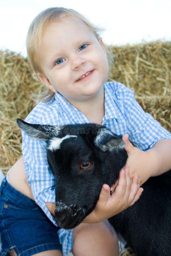 Bambino felice che abbraccia la sua capra. immagini stock libere da diritti