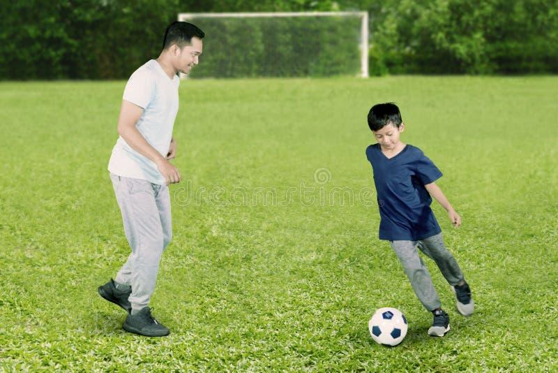 Bambino felice che fa gli esercizi di calcio con suo padre immagini stock