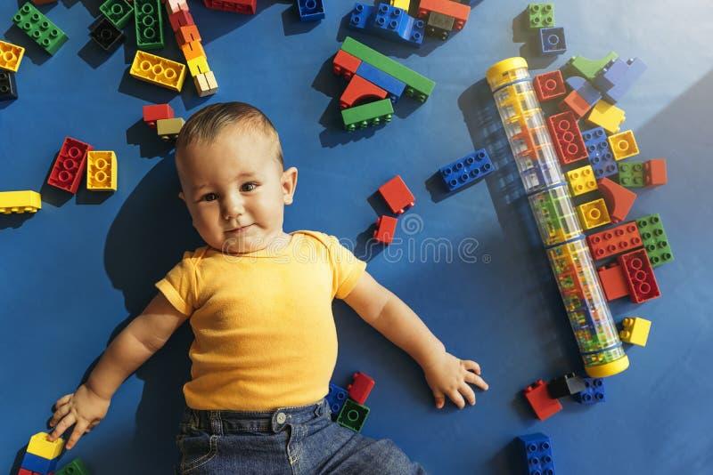 Bambino felice che gioca con i blocchetti del giocattolo immagini stock
