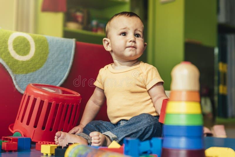 Bambino felice che gioca con i blocchetti del giocattolo immagine stock