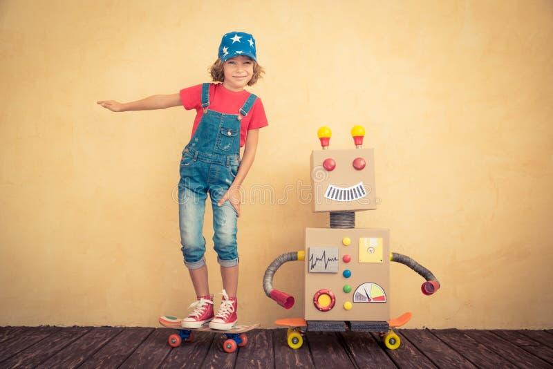 Bambino felice che gioca con il robot del giocattolo immagine stock