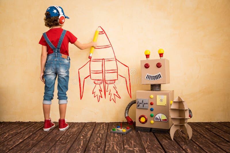 Bambino felice che gioca con il robot del giocattolo immagine stock libera da diritti