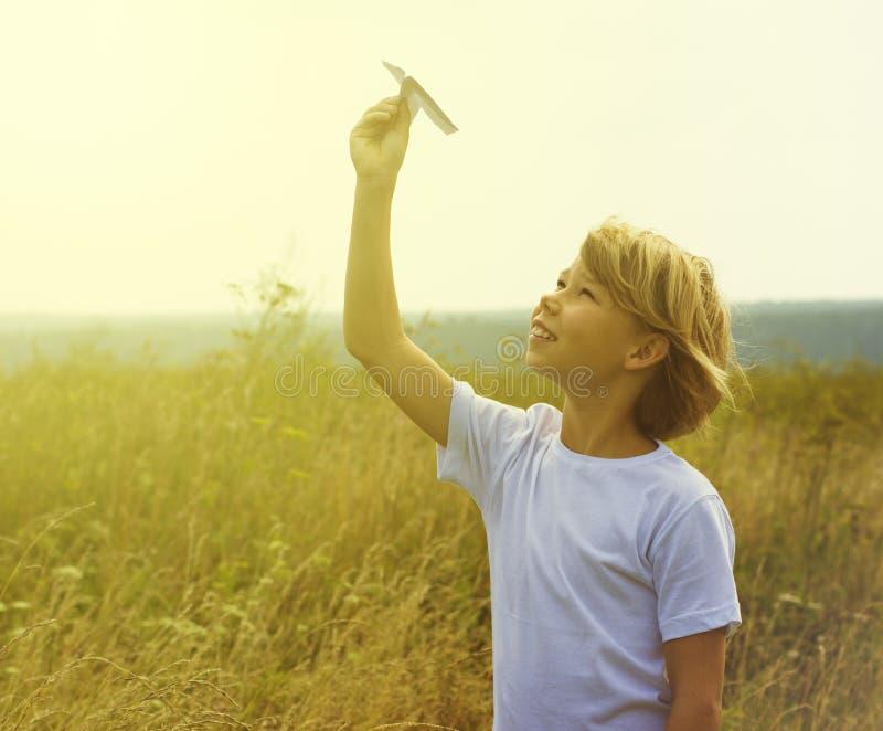Bambino felice che gioca con l'aeroplano del giocattolo fotografie stock