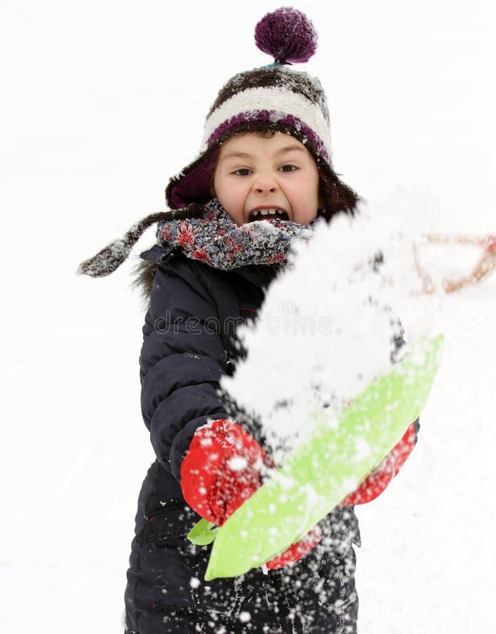 Bambino felice che gioca con la neve nell'inverno fotografia stock