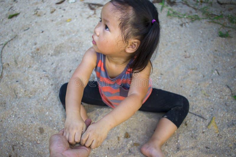 Bambino felice che gioca con la sabbia, famiglia asiatica divertente in un parco immagini stock libere da diritti