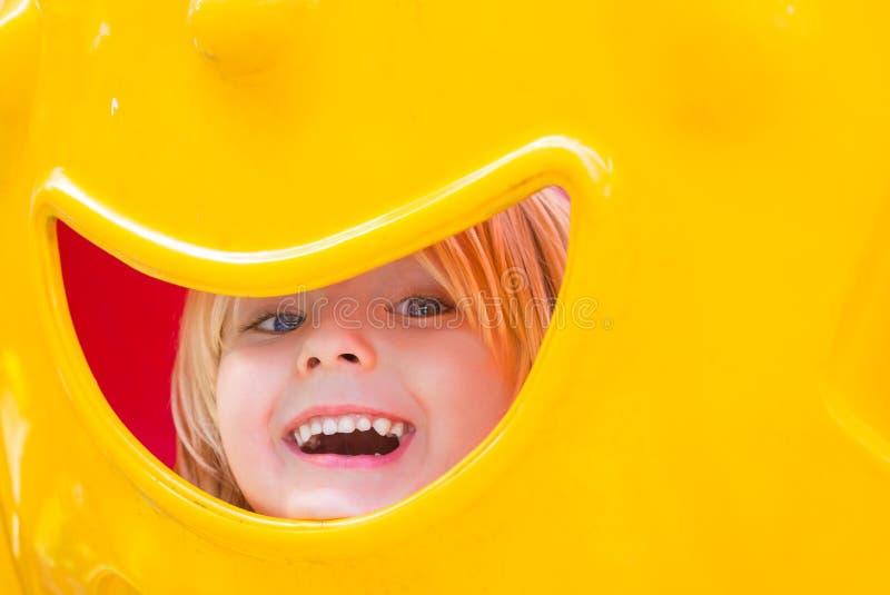 Bambino felice che gioca e che dà una occhiata in un campo da giuoco immagine stock