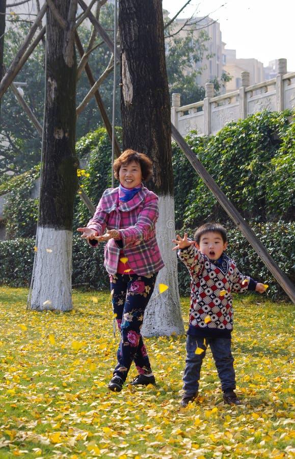 Bambino felice che gioca le foglie dorate del ginkgo immagine stock libera da diritti