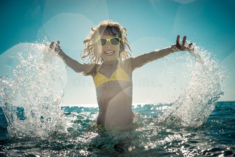 Bambino felice che gioca nel mare immagine stock libera da diritti