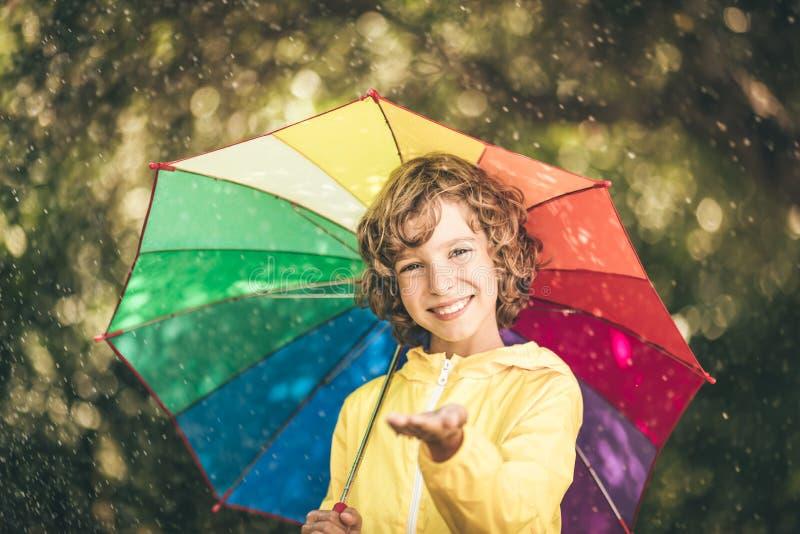 Bambino felice che gioca nella pioggia fotografie stock libere da diritti