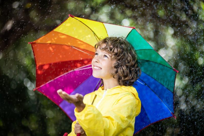 Bambino felice che gioca nella pioggia fotografie stock