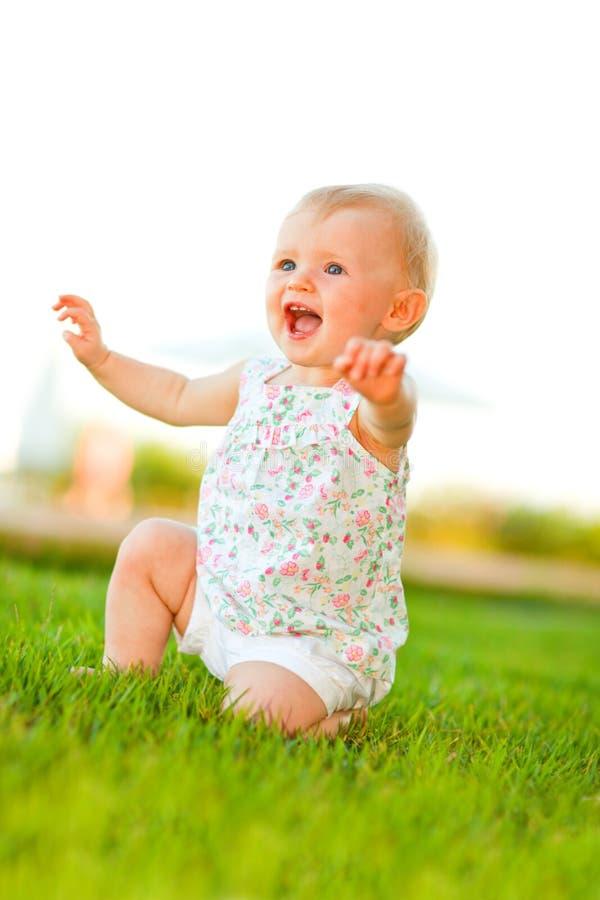 Bambino felice che gioca sull'erba fotografie stock