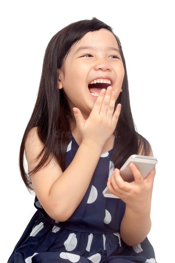 Bambino felice che gioca sullo smartphone fotografia stock