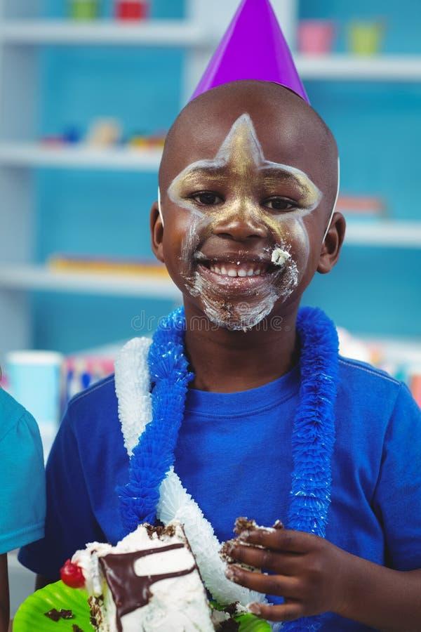 Bambino felice che mangia torta di compleanno fotografia stock libera da diritti