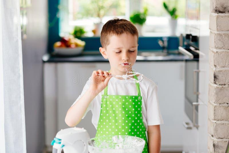 Bambino felice che prova pasta dolce dal battitore del miscelatore immagini stock libere da diritti