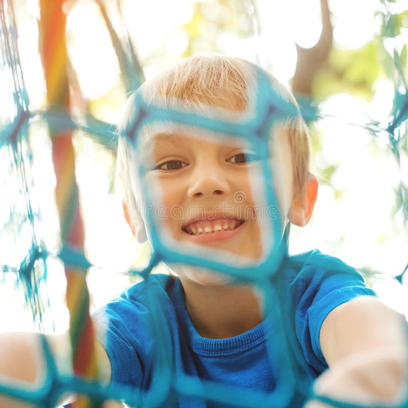 Bambino felice che scala sulle corde di un campo da giuoco Ragazzino allegro che gioca sul campo da giuoco moderno Bambino sorrid fotografia stock libera da diritti