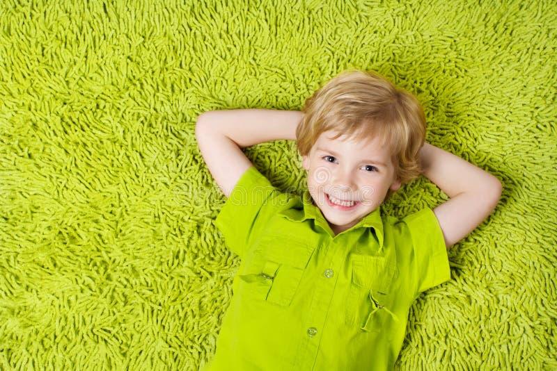 Bambino felice che si trova sui precedenti verdi della moquette immagini stock libere da diritti