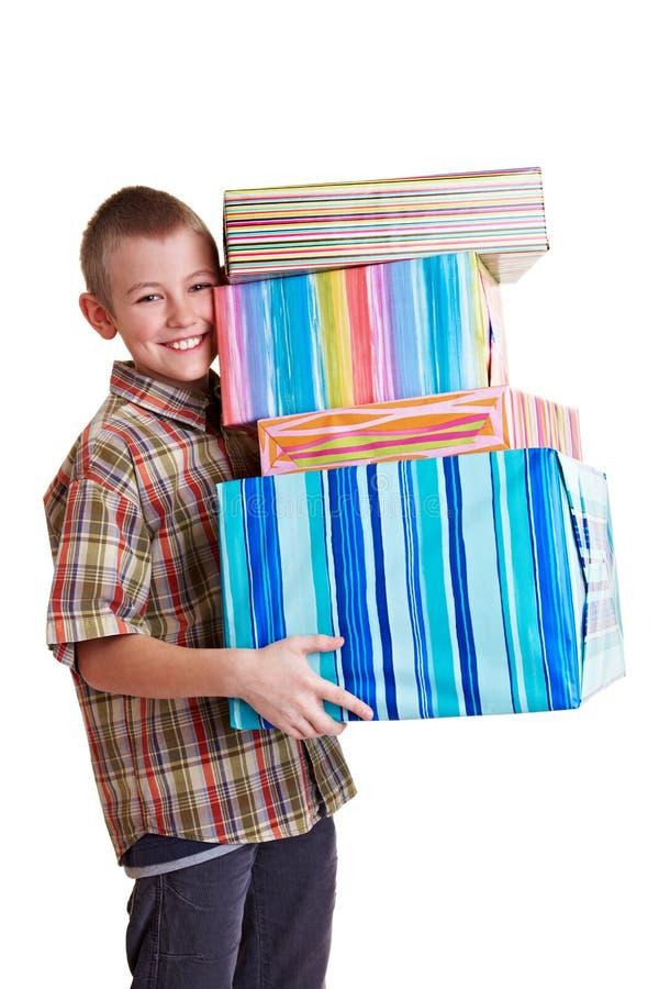 Bambino felice che trasporta molti regali fotografia stock libera da diritti