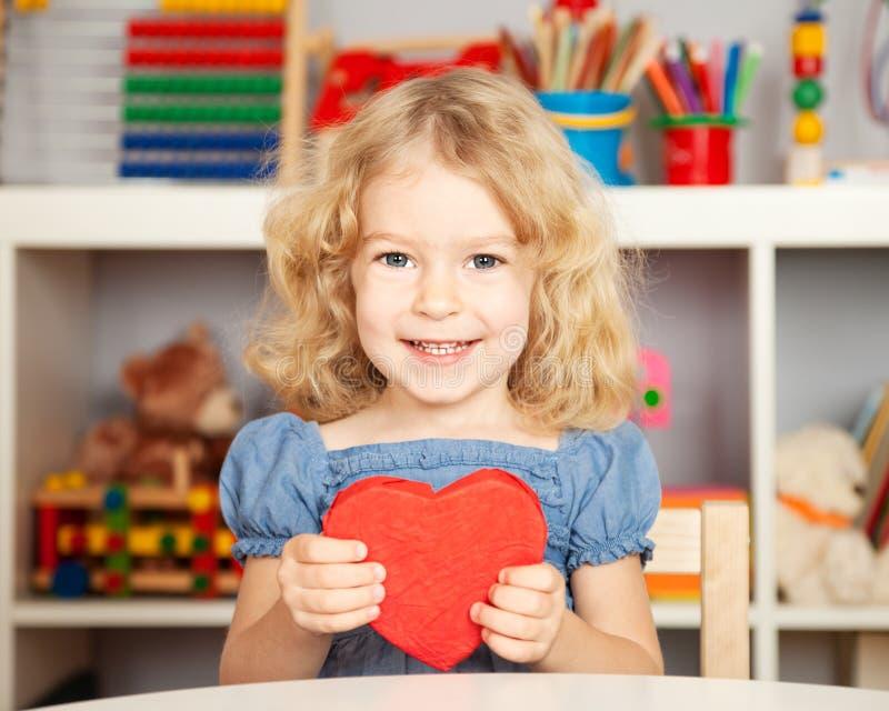 Bambino felice con cuore di carta immagine stock