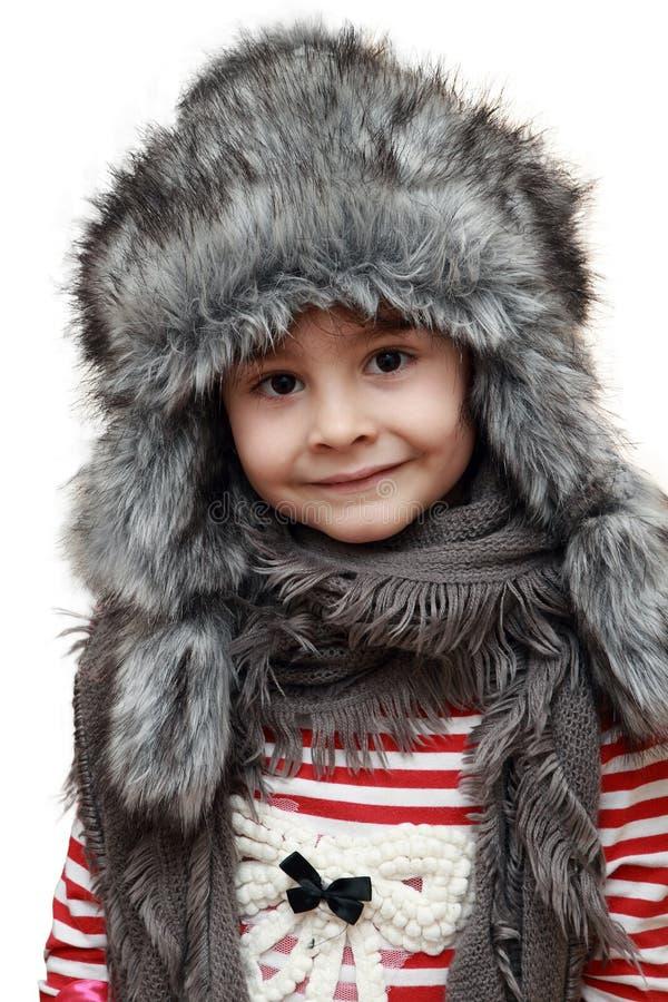 Bambino felice con il cappello simile a pelliccia di inverno immagini stock libere da diritti