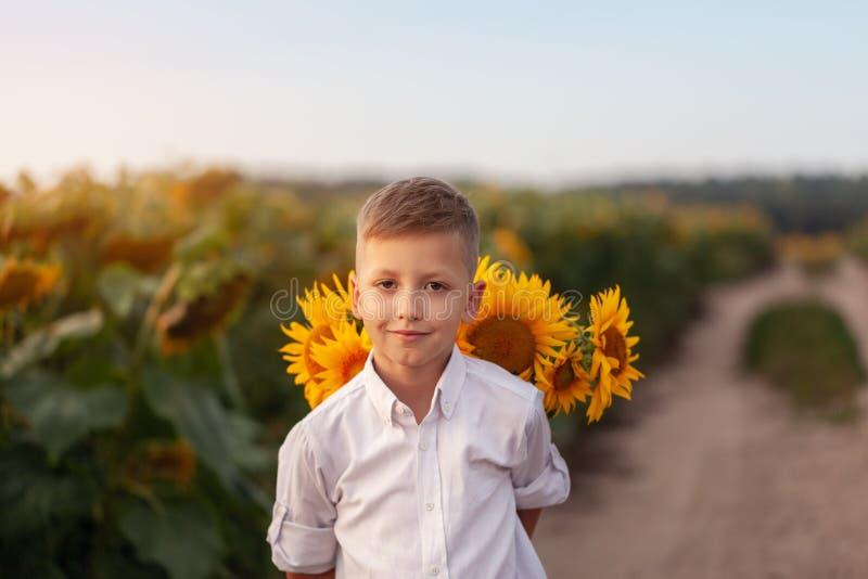 Bambino felice con il mazzo di bei girasoli nel giacimento del girasole di estate sul tramonto Giorno di madre fotografia stock libera da diritti