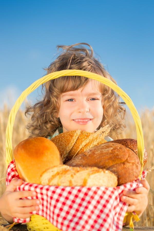 Bambino felice con la merce nel carrello del pane immagine stock