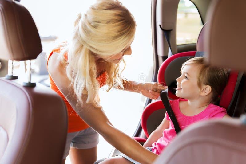 Bambino felice della legatura della madre con la cinghia della sede di automobile fotografia stock libera da diritti